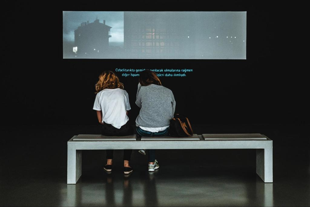 A person sitting on a bench in front of a television reading video subtitles