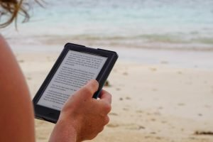 A person sitting at a beach reading content on a tablet
