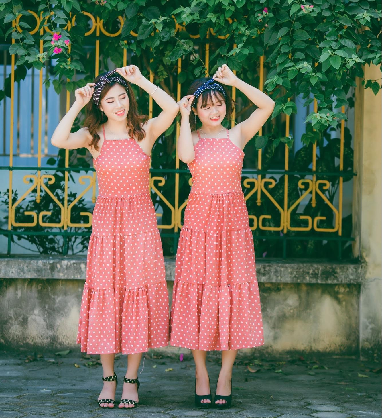 Twin girls in red dresses standing in front of a flower